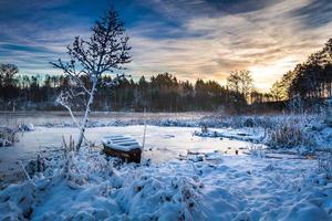 Frozen lake in winter at sunrise