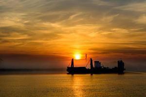 barco de pesca, deixando o porto em um fundo nebuloso.