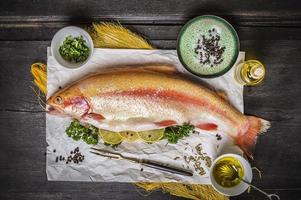 raw trout on dark wooden table with herb and lemon