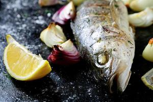 Delicious fried sea bass with lemon and onion on tray