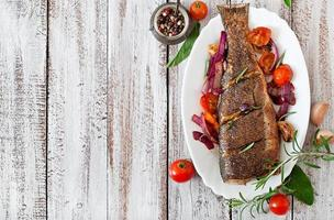Roasted seabass with vegetables on an old wooden background