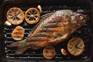 carp with lemon, onion, spices on grill pan, top view
