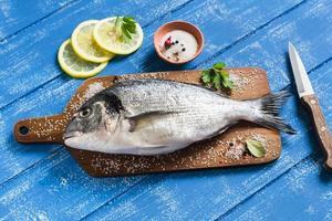 fresh Dorado fish and lemon on a blue wooden background photo