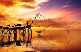 silueta de pescador en redes de pesca foto