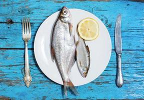 fresh fish on the plate, table setting, wooden background