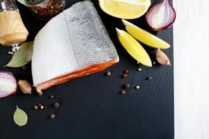 Raw Salmon steak on slate with lemon and spices photo