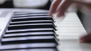 mão de mulher tocando um sintetizador de teclado controlador midi close-up. video