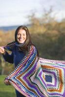 Smiling woman wrapped in blanket outdoors