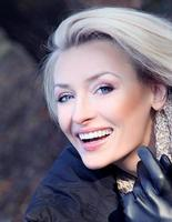 Photo of attractive blonde lady posing, smiling.