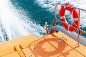 Salvavidas rojo colgando de las rejas del bote de rescate foto