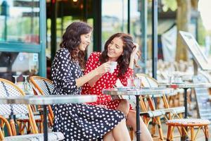 Hermosas hermanas gemelas tomando café en París