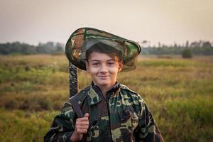 menino sorridente com espingarda de caça em pé no campo