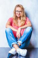 blonde girl wearing glasses poses while sitting on the floor
