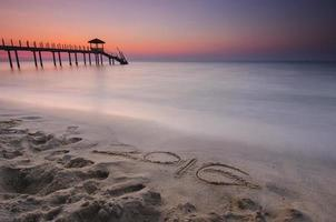 word 2016  written on sand and fisherman cottage photo