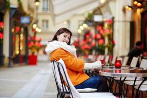 Hermosa joven en un café parisino al aire libre
