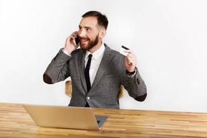 Cheerful man talks on the phone and holds bank card