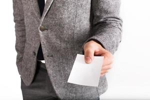 Man in gray business suit holds blank white card