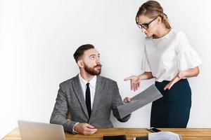 Male and female businesspeople converse over desk on white background