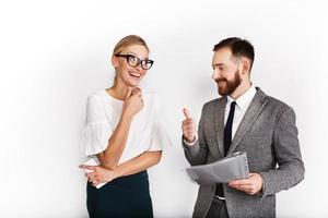 Socios comerciales alegres vestidos con traje de oficina sobre fondo blanco. foto