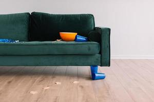 Round orange plastic bowl on green sofa
