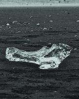 Piece of ice on black sand