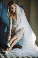 Beautiful bride in a veil sits on chair and fixes her wedding shoes photo