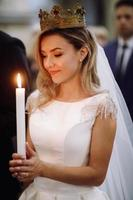 Europe, 2018 - Bride holds candle during engagement ceremony.