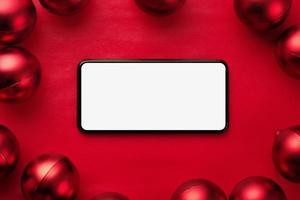 maqueta de teléfono inteligente rodeada de adornos rojos