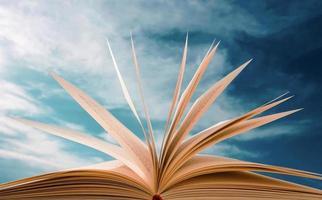 libro abierto con el telón de fondo de un cielo nublado