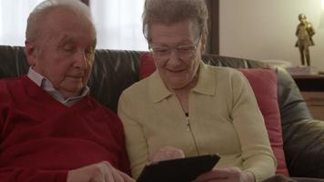 An elder senior couple sitting on the couch with a tablet while they are browsing the internet, watching videos and commenting the contents