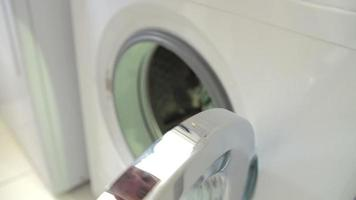 Slow Motion Shot Of Man Putting Laundry Into Washing Machine