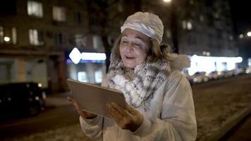 Mujer feliz viendo algo en la almohadilla durante la caminata nocturna