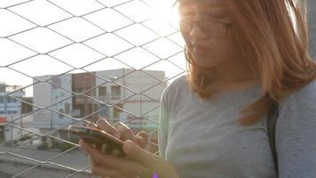 asiatisches Mädchen mit Smartphone auf Überführung