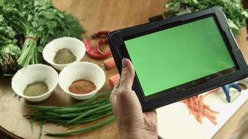 The woman cooks food using tablet