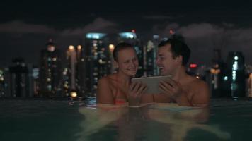 Nachtansicht des jungen schönen Paares im Schwimmbad, das in Tablette auf dem Dach des Wolkenkratzers und der Stadtlandschaft beobachtet. Kuala Lumpur, Malaysia