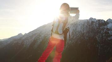 Hiker reaches mountain peak, takes picture with digital tablet video