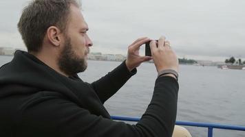 vista lateral de um homem bonito tirando fotos enquanto faz turismo em são petersburgo, na Rússia. homem usando seu smartphone, câmera lenta