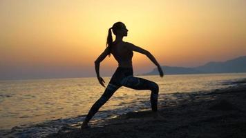 junge Frau der Silhouette, die Yoga am Strand bei Sonnenuntergang praktiziert
