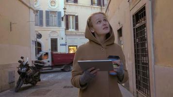 Frau mit Block und Kaffee, die in der Straße gehen