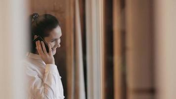 junge Frau telefoniert am Fenster