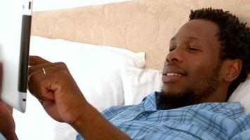 Man relaxing in his bed using tablet pc video