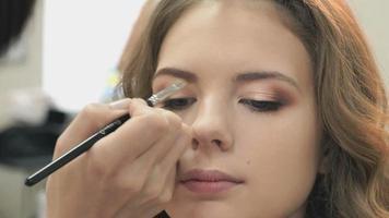 maquiador fazendo maquiagem para uma jovem modelo