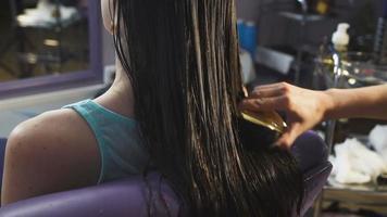 linda garota em um salão de beleza para cabelo recebe procedimento de saúde