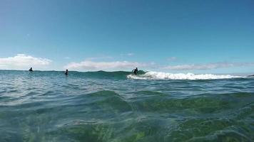 Cámara lenta bajo el agua: joven surfista surfeando en una ola