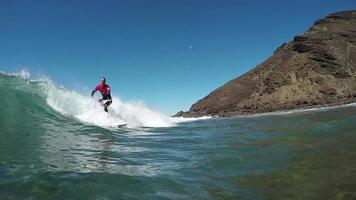 Cámara lenta bajo el agua: surfista surfeando en una gran ola rompiendo