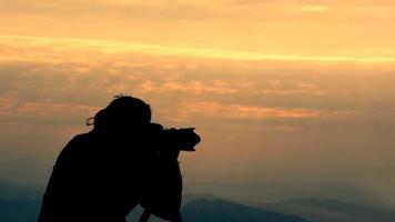 photographe silhouette tir au sommet de la montagne au lever du soleil vidéo hd video
