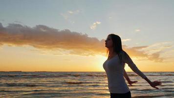 mujer joven con una hermosa figura calentando antes de un trote nocturno. en la playa al atardecer