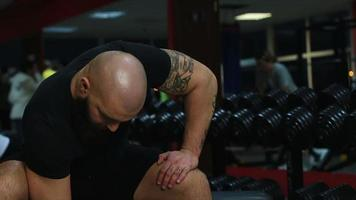 Tattooed muscular male athlete doing dumbbell exercises, working out in gym
