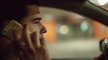 homem sentado no carro e falando no celular