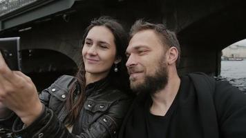 glückliche lächelnde Liebhaber, die selfie nehmen, mit Smartphone. Bootstour in St. Petersburg unter einer Brücke. Zeitlupe